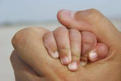 De baby dient volwassen hand in Stock Fotografie