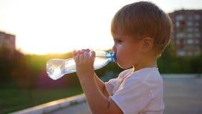 De baby drinkt water in openlucht van fles De tijd van de zonsondergang stock footage