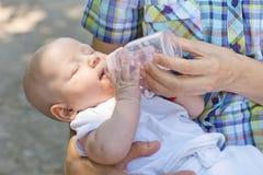 De baby drinkt water van fles Royalty-vrije Stock Afbeeldingen