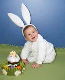 De baby in een kostuum van de hazen met een Pasen Pasen koekt Stock Foto's