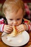De baby eet de heerlijke pannekoeken stock afbeeldingen