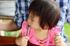 De baby eet met lepel stock foto's