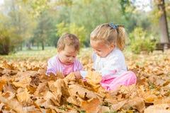 De baby en het meisje hebben pret met de herfstbladeren Royalty-vrije Stock Afbeeldingen