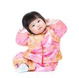 De baby heeft grappige houding met het traditionele kostuum van China stock afbeelding