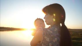 De baby houdt jonge moeder in haar wapens en het glimlachen Langzame Motie stock videobeelden