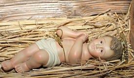 De baby Jesus wordt gelegd in de wieg in een trog Royalty-vrije Stock Fotografie
