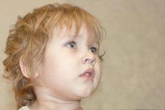 De baby kijkt met hartstocht en rente omhoog en aan de kant stock foto's