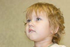 De baby kijkt met hartstocht en rente omhoog en aan de kant stock fotografie