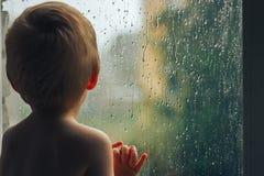 De baby kijkt om door het venster te regenen die zich met rug bevinden Royalty-vrije Stock Fotografie