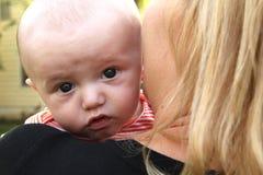 De baby kijkt over zijn moeder` s schouder Stock Afbeeldingen