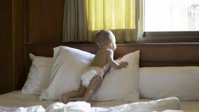 De baby kijkt uit het venster terwijl status op het bed Zuigeling 8 maand royalty-vrije stock afbeeldingen