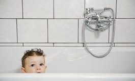 De baby kijkt uit van badkuip Stock Foto's