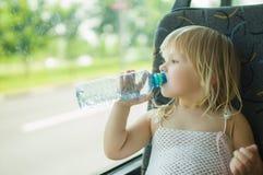 De baby in kleding drinkt de bus van de waterrit Stock Fotografie