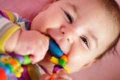 De baby knaagt aan een stuk speelgoed Royalty-vrije Stock Foto's