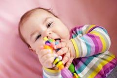 De baby knaagt aan een stuk speelgoed Stock Foto
