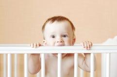 De baby knaagt aan wit bed Stock Fotografie