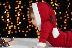 De baby kruipt in Kerstmisdecoratie, gekleed als Kerstman, boke lichten op donkere achtergrond, het concept van de de wintervakan Stock Afbeeldingen