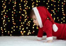 De baby kruipt in Kerstmisdecoratie, gekleed als Kerstman, boke lichten op donkere achtergrond, het concept van de de wintervakan Royalty-vrije Stock Foto