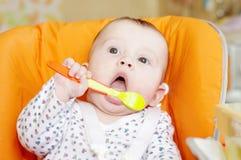 De baby leert om met lepel te eten stock afbeeldingen