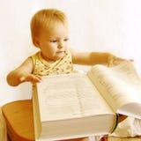De baby leest het boek Stock Afbeelding