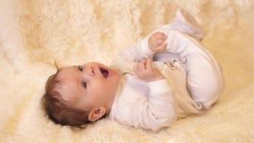De baby in lichaam ligt op zijn rug, die met zijn handen, benen en het spreken spelen stock videobeelden