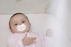 De baby ligt in de voederbak met fopspeen stock fotografie