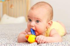 De baby ligt en knaagt aan stuk speelgoed Stock Afbeeldingen