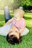 De baby ligt op het gras met haar papa Stock Foto's