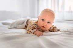 De baby ligt op het witte bed royalty-vrije stock afbeelding