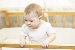 De baby 8 maanden in wit kijkt uit de wieg De leuke baby kent de wereld, klampt een nieuwsgierig kind zich aan de rand van de voe royalty-vrije stock fotografie