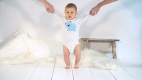 De baby met grote blauwe ogen en blond haar leert te gaan stock videobeelden