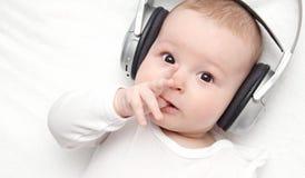 De baby met hoofdtelefoon ligt op rug Royalty-vrije Stock Afbeelding