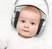De baby met hoofdtelefoon ligt op rug Stock Afbeelding