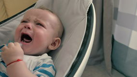De baby met model schreeuwt in de wieg en de moeder neemt hem op handen
