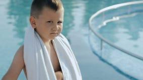 De baby met witte handdoek dichtbij het zwembad glimlacht stock videobeelden