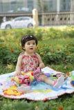 De baby ontspant op gras met speelgoed Stock Fotografie