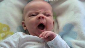 De baby ontwaakt en kijkt stock footage