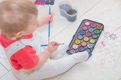 De baby op vloer het spelen met zijn verven royalty-vrije stock afbeeldingen