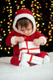 De baby pakt giftdozen met Kerstmisdecoratie uit, gekleed als Kerstman, boke lichten op donkere achtergrond, het concept van de d Stock Afbeeldingen
