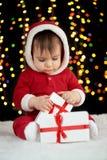 De baby pakt giftdozen met Kerstmisdecoratie uit, gekleed als Kerstman, boke lichten op donkere achtergrond, het concept van de d Stock Foto