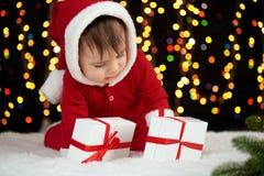 De baby pakt giftdozen met Kerstmisdecoratie uit, gekleed als Kerstman, boke lichten op donkere achtergrond, het concept van de d Royalty-vrije Stock Fotografie