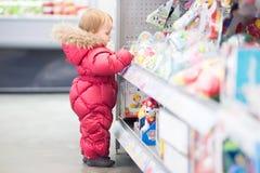 De baby plukt een stuk speelgoed bij de opslag Royalty-vrije Stock Afbeelding