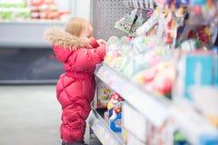 De baby plukt een stuk speelgoed bij de opslag Stock Afbeelding