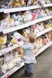 De baby plukt een stuk speelgoed bij de opslag Royalty-vrije Stock Foto's