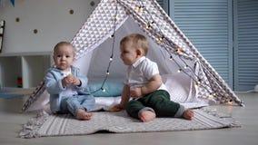 De baby probeert om de koekjes van een ander kind dichtbij de tent van het kind weg te halen stock video