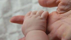 De baby ` s dient de hand van een volwassene in