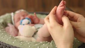 De baby` s voet is in mamma` s hand stock videobeelden
