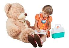 De baby speelt arts, behandelt een beer Stock Fotografie