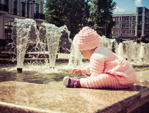 De baby speelt bij de fontein Stock Afbeelding