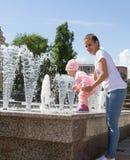 De baby speelt bij de fontein Stock Afbeeldingen